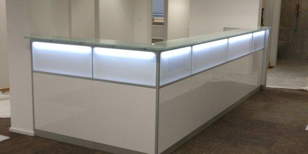Weiße Empfangstheke mit Hochglanz und Beleuchtung bei Temporis Personal in der Schweiz