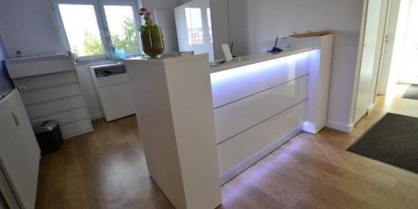 Weißer Empfangstresen mit Beleuchtung und Glanzfront in Wuppertal Cronenberg Physiotherapie Mießner & Brosge